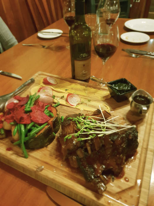 Image of a table with a cutting board and a selection of meats and vegetables and two small jars with sauce
