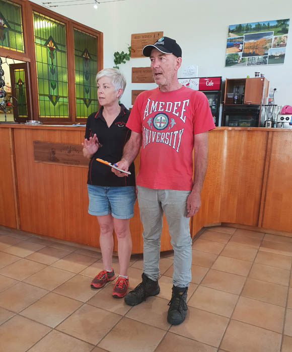 Image of a man in a red tshirt and grey trousers standing next to a woman in a black tshirt and blue denim shorts they are explaining their wine making process to a group