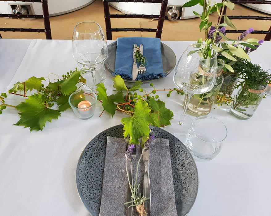 Image of a tabel setting with grey plates and wine glass and vine leaves for decoration