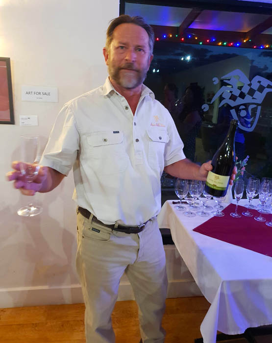 Images of a bearded midldle aged man dressed in short sleeved shirt and camel coloured trousers holding a bottle of wine and a glass offering it to someone out of picture