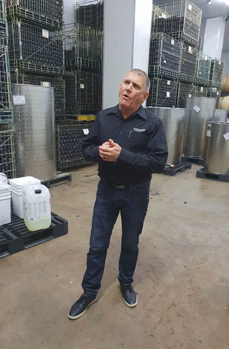 Image of a man dressed in adrk long sleeve shirt and trousers standing in front of wine making equipment he is talking about wine making