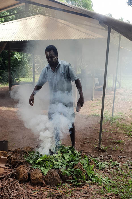 Image of an Indigenous Australian man standing behind a firepit with green leaves with smoke coming from it he is waving the smoke onto himself as part of the smoking ceremony