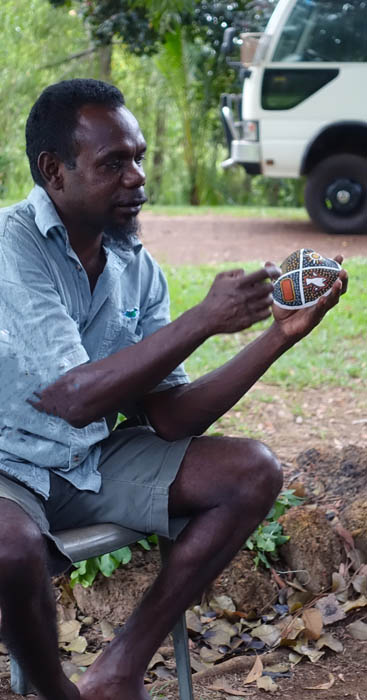 Image of an Indigenous Australian man wearing a blue shirt and grey shorts sits on a chair holding a painted mussel shell