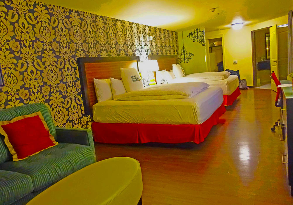 Image of a hotel room with two large beds and pillows