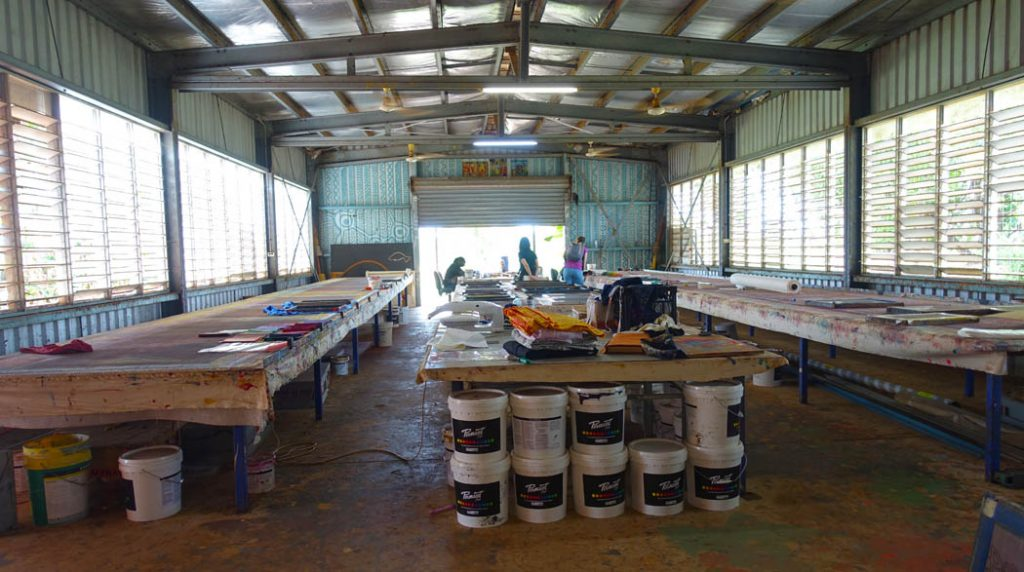 Image of a large open shed with three long tables and large containers of paint - the shed is an artists studio
