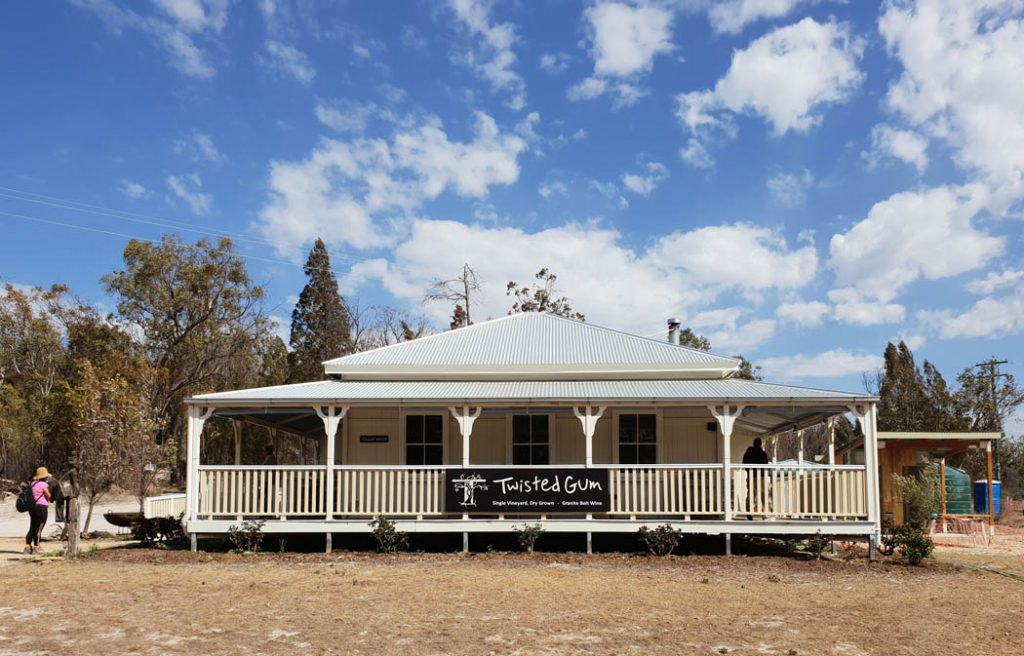 Image of a Queensland style house with wrap around verandas and a corrugated iron roof and sign on the veranda palings that says Twisted Gum