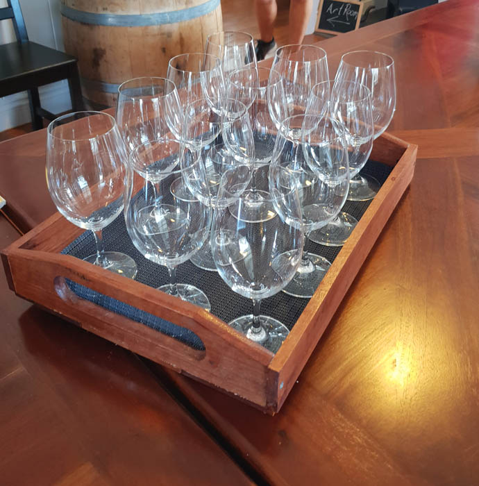 Image of a wooden tray with a dozen empty wine glasses