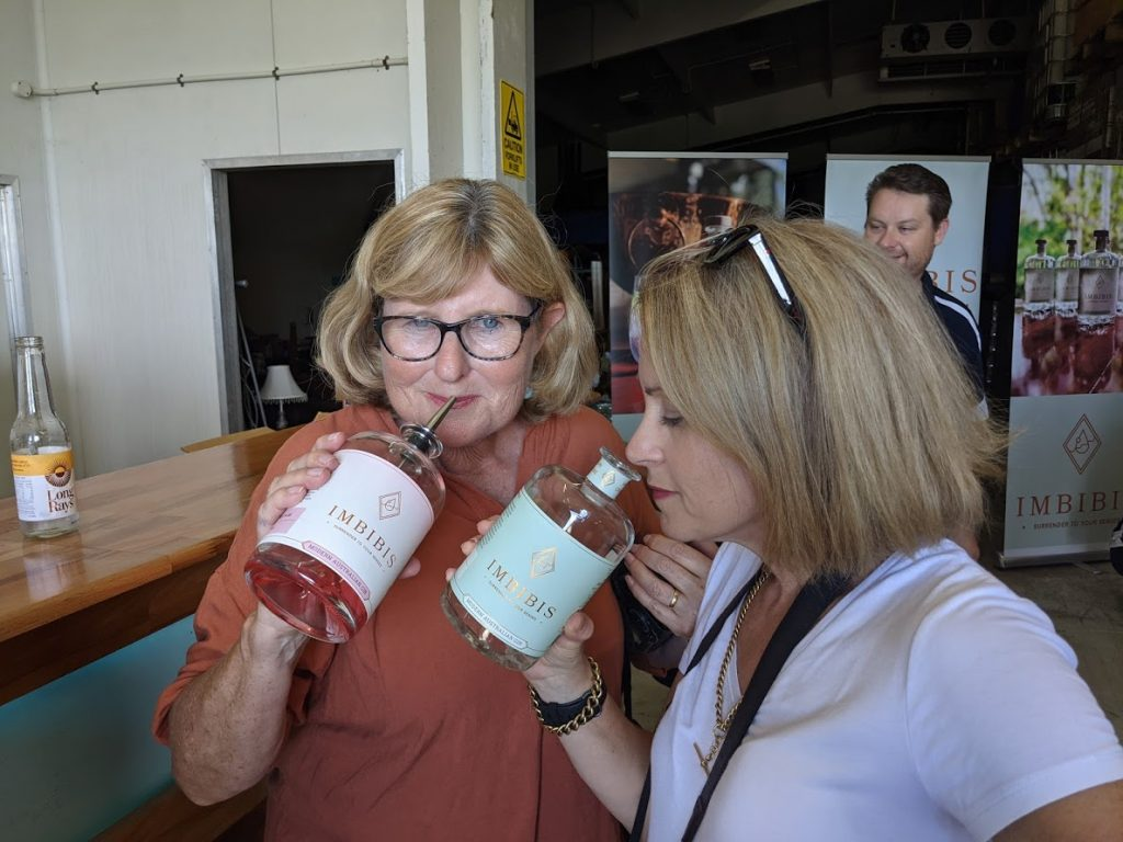 Image of two women standing close to each other holding a bottle of gin as they are sniffing the contents