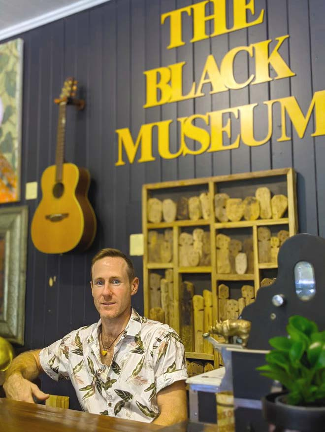 Image of a man in a short sleeved shirt sitting in front of a sign on the black wall behind him with the words The Black Museum in yellow letters