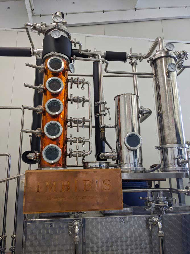 Image of a copper gin still with pipes leading to another silver coloured still