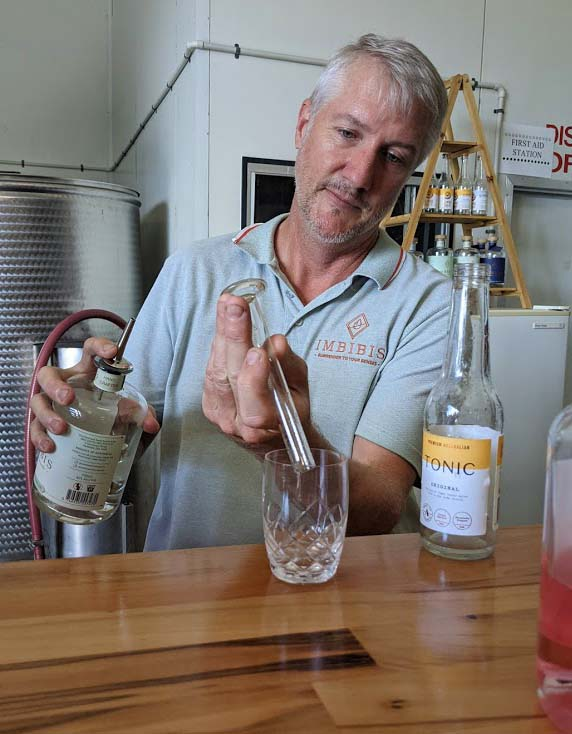 Image of a man standing behind a counter measuring a portion of gin into a glass on the counter