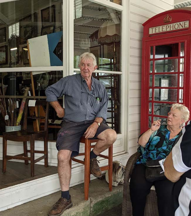 Image of an older white haired man sitting on a stool outside a shopfront with a red British telephone box behind him