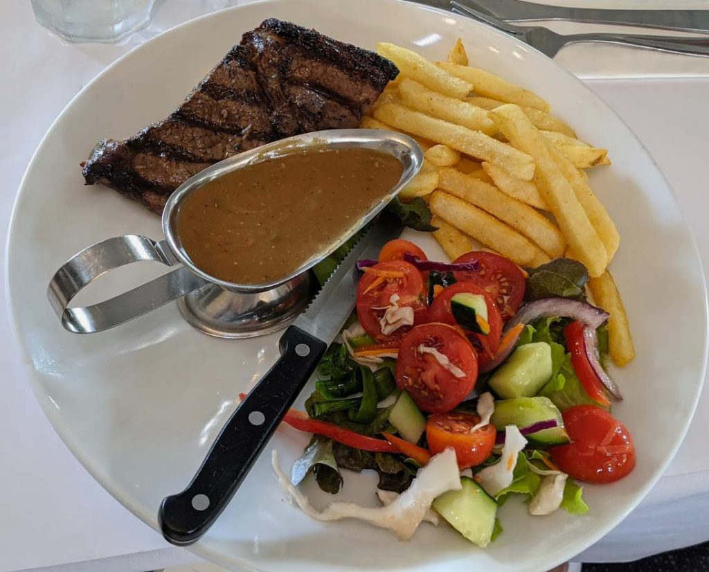 Image of a white dinner plate with a piece of steak a serving of chips and salad and a jig filled with gravy
