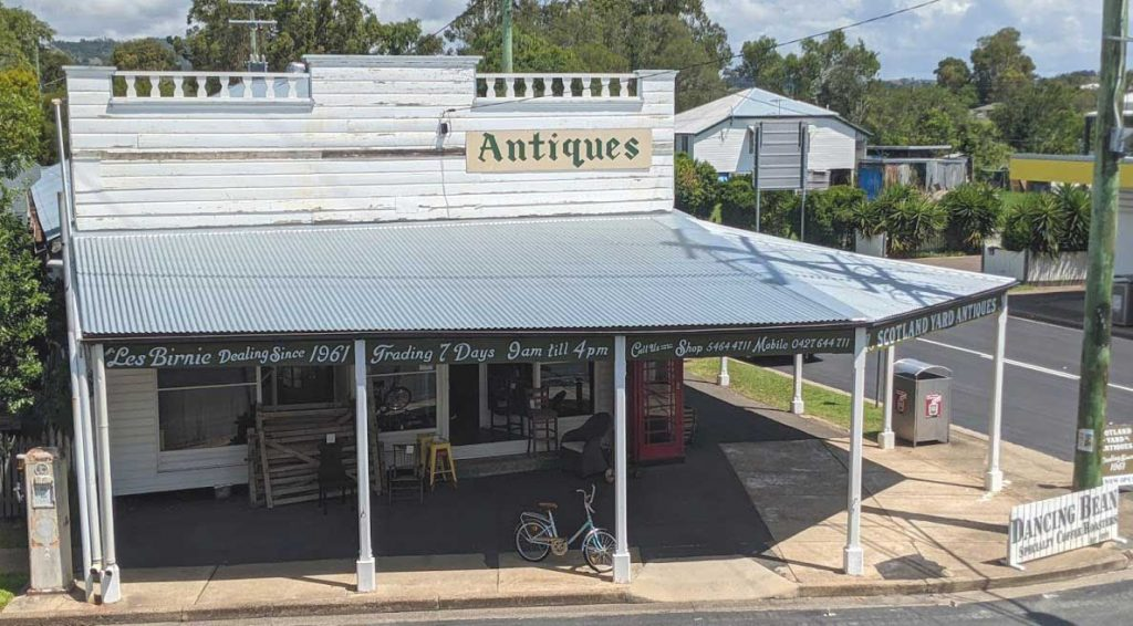 Image of the exterior of an Antiques store in a country town with a silver corrugated steel rof and signs around the roof advsing store opening hours