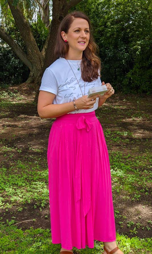 Image of a woman with lng red hair wearing a white t short with a vivid pink skirt