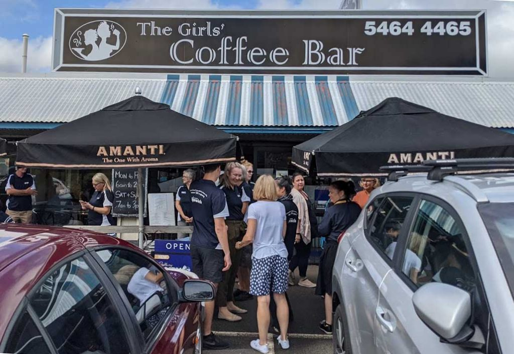 Image of a people standing in front of the entrance to a cafe with a sign above saying the Girls' Coffe Bar
