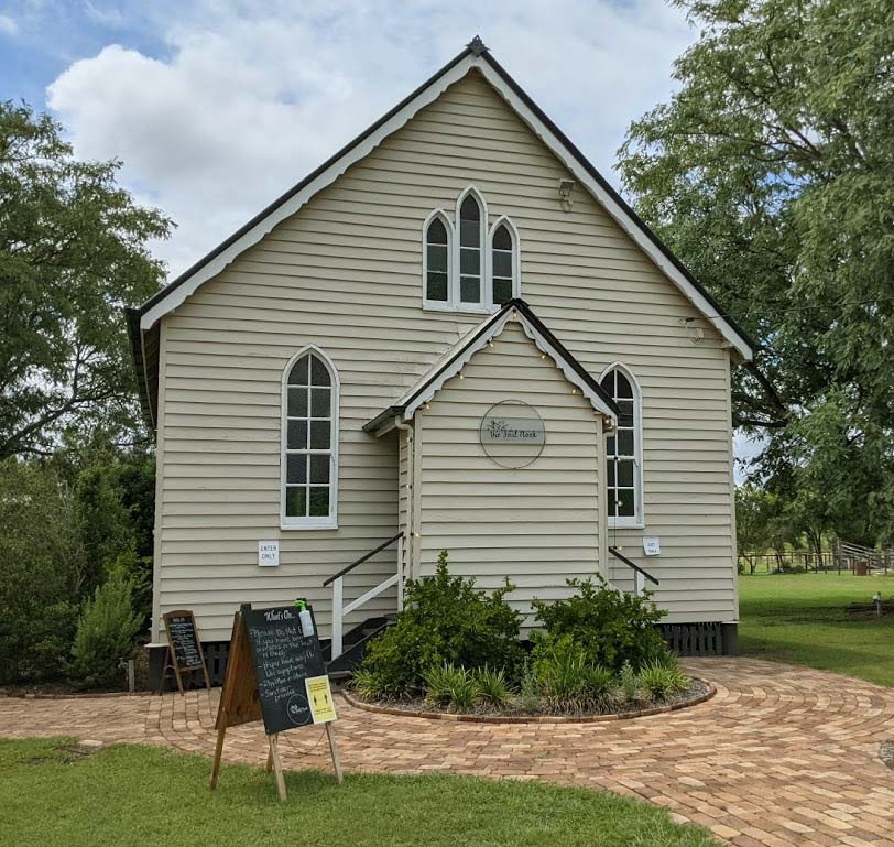 Image of the front of a country church cream in colour with white window trims