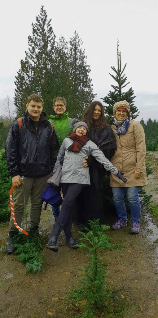 Image of a group of people standing in front of a tree in the ground that is shaped like a Christmas tree