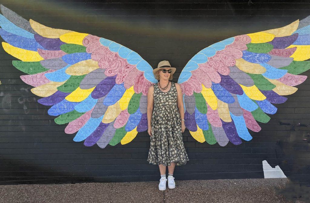Image of a woman standing between the wings painted on tside of a building
