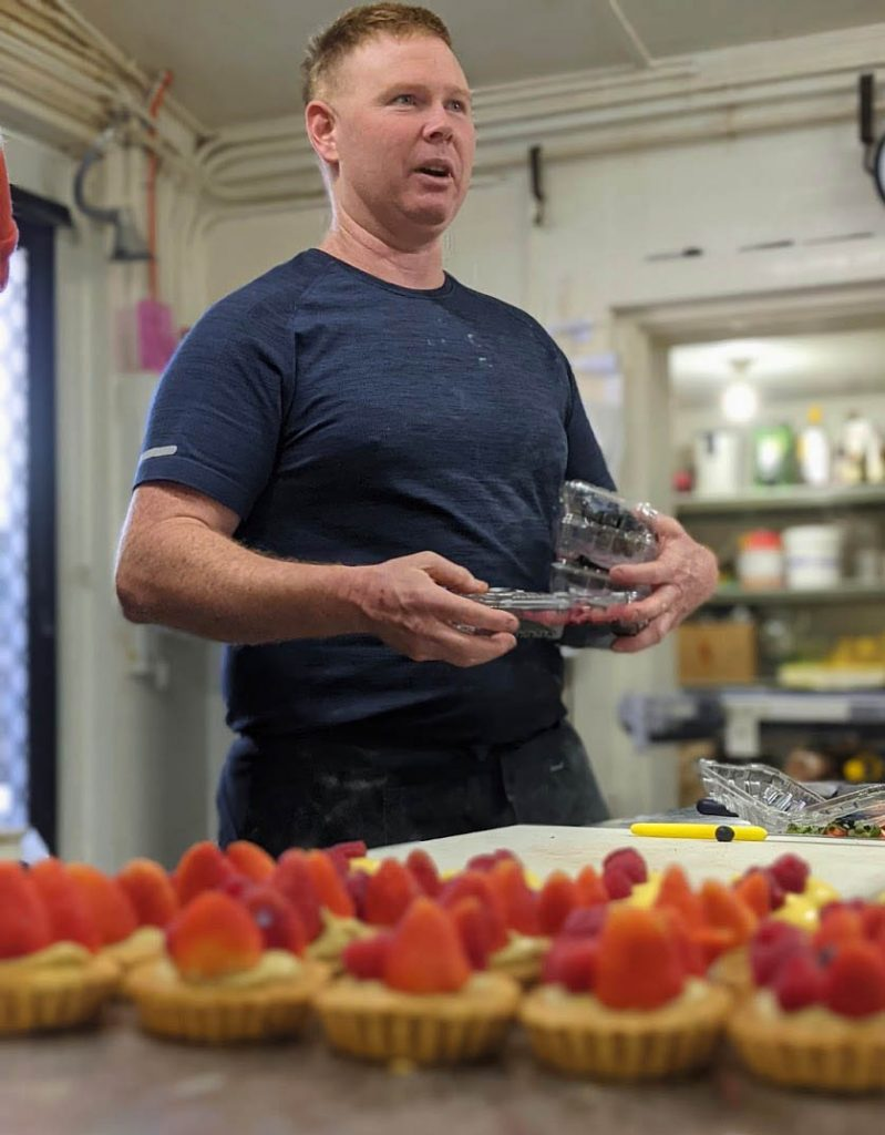 Image of a man wearing a blue t shirt and dark apron holding plastic containers filled with berries