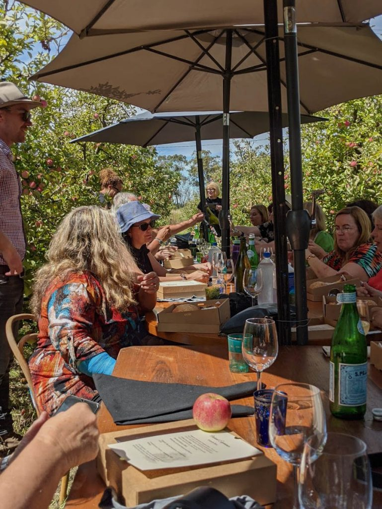Image of people in an orchard sitting around a table under large umbrellas