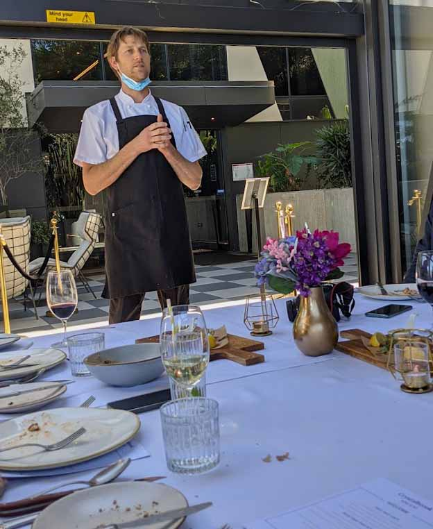 Image of a man standing in front of a long table wearng an apron on top of his clothes signifying he is a chef